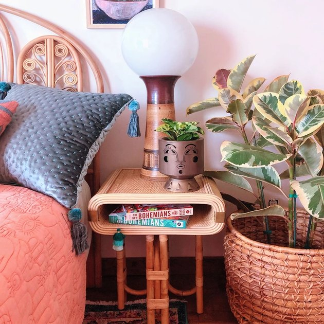 side table near bed with lamp and planter and plant nearby