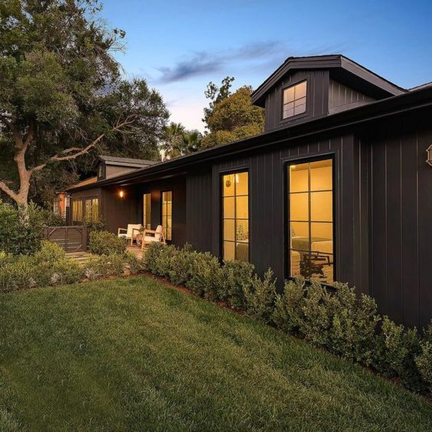 black home exterior with green lawn and steel-framed windows
