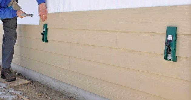 Installing fiber cement planks siding.