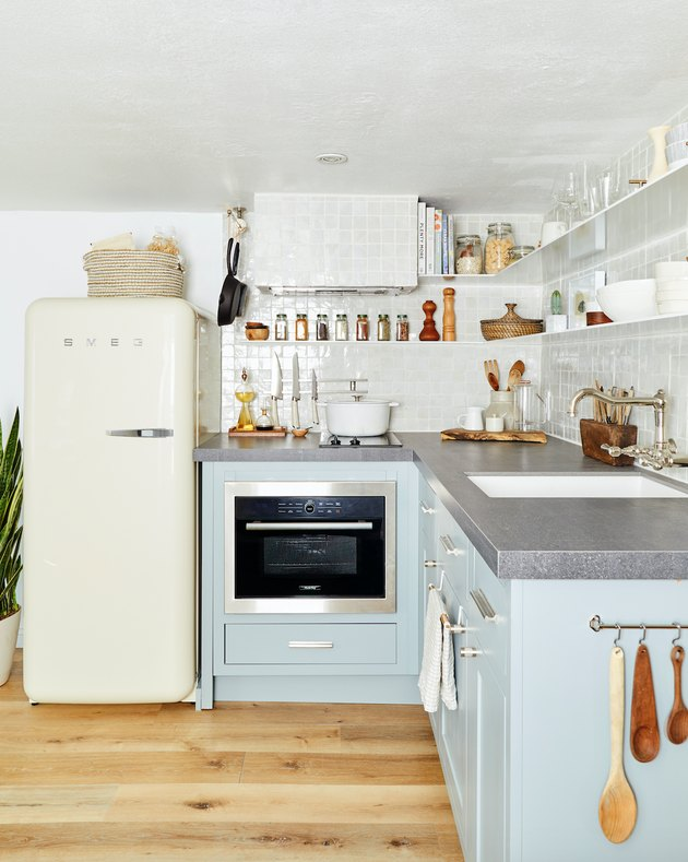 small kitchen layout idea with blue cabinets and open shelving