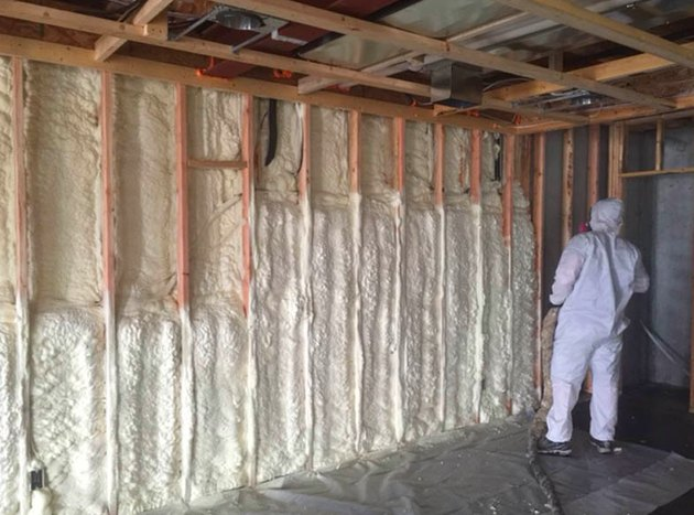 Spraying foam insulation in the basement.