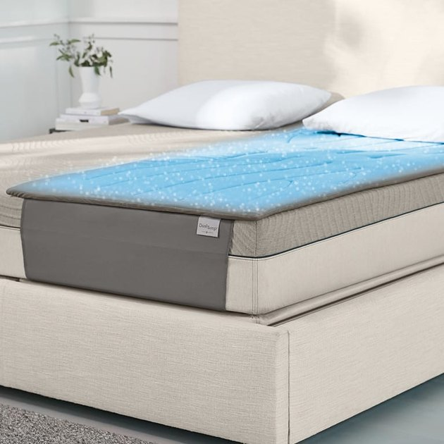 Blue mattress pad on one half of bed