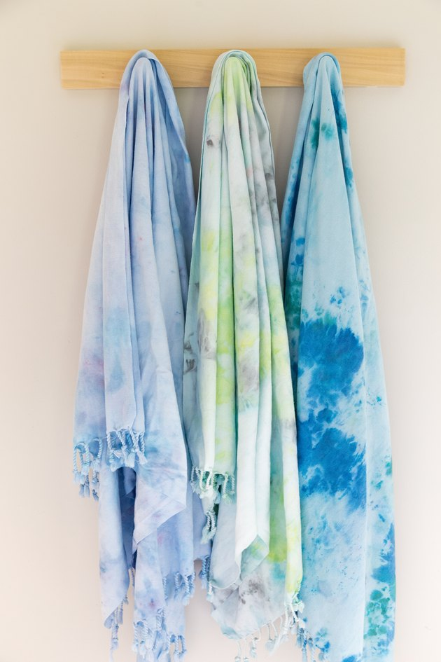 Tie-dyed towels hung on wood rack