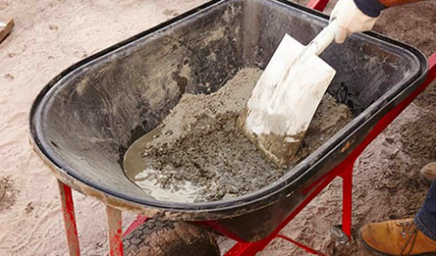 Mixing concrete in a wheelbarrow.