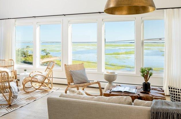 salon côtier avec fauteuil à bascule en osier, chaises longues en rotin, canapé beige, suspension en laiton, grandes fenêtres avec rideaux transparents.