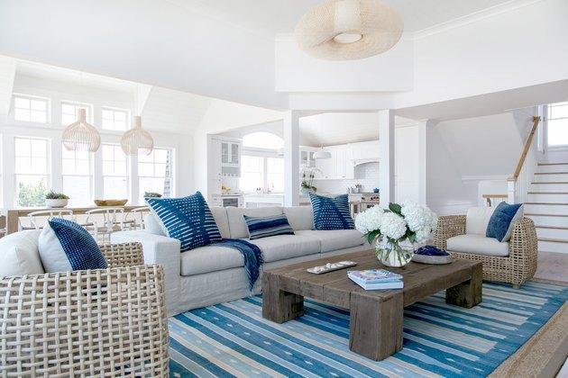 salon côtier avec chaises, canapé blanc cassé, tapis rayé bleu, coussins bleus, murs blancs, parquet.