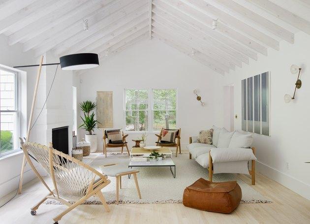 salon côtier avec chaise Acapulco en osier, pouf en cuir, canapé blanc, plafonds voûtés blancs, parquet clair.