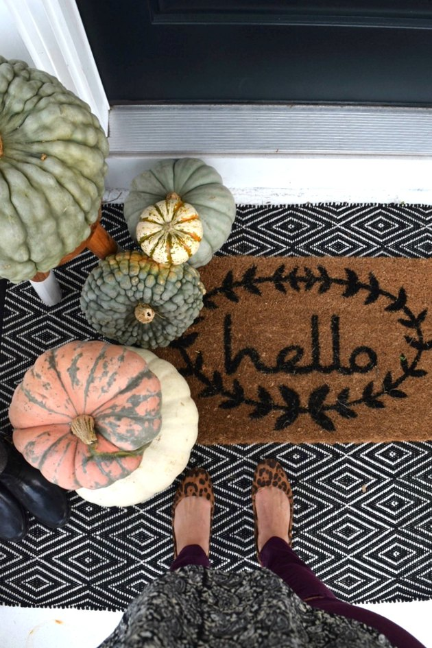Hello fall doormat with black and white rug and pumpkins