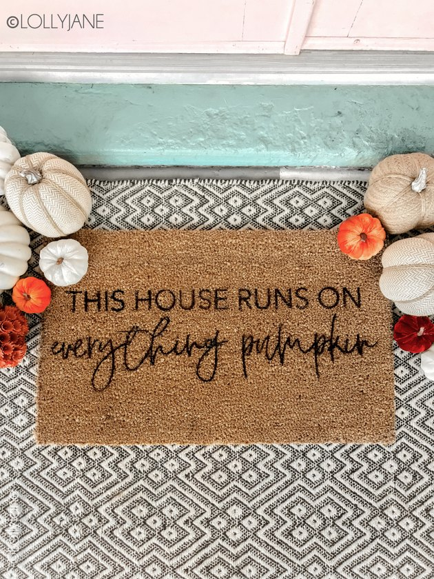 Stenciled fall doormat with patterned rug and pumpkins