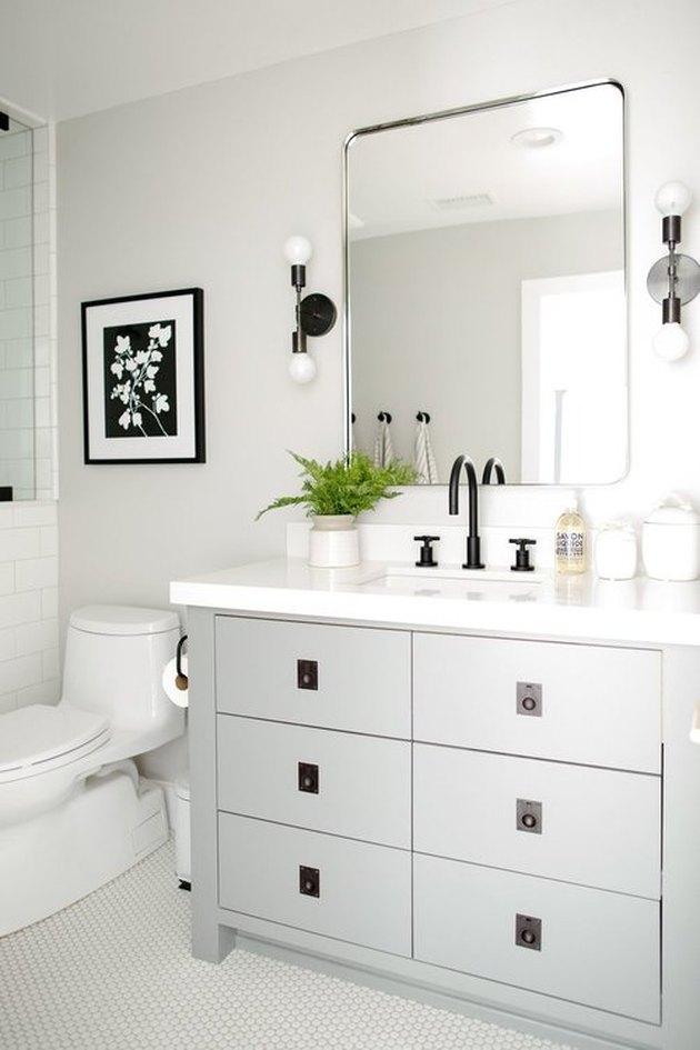 small bathroom lighting idea with wall sconces and gray cabinets