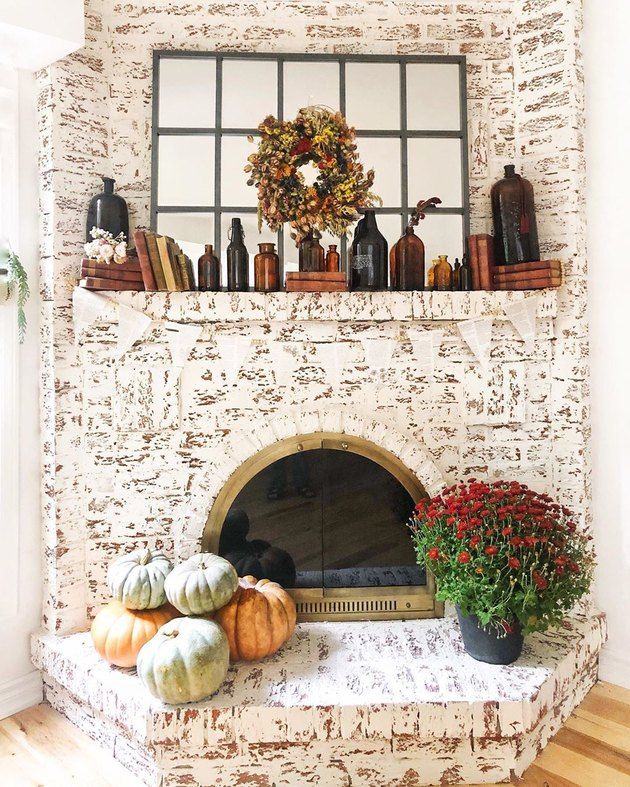 orange and green fall pumpkins on brick fireplace