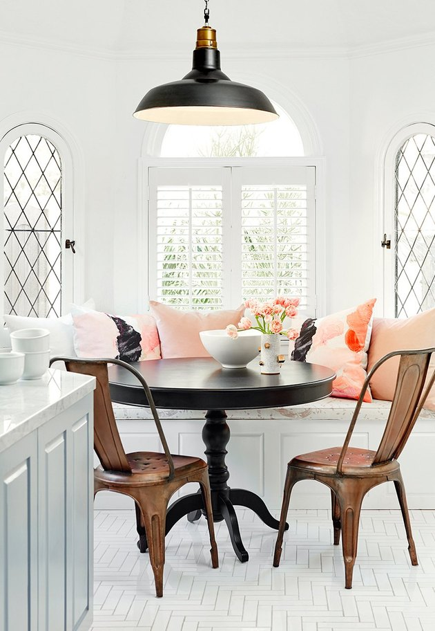 small dining room with black table and copper chairs and built-in bench