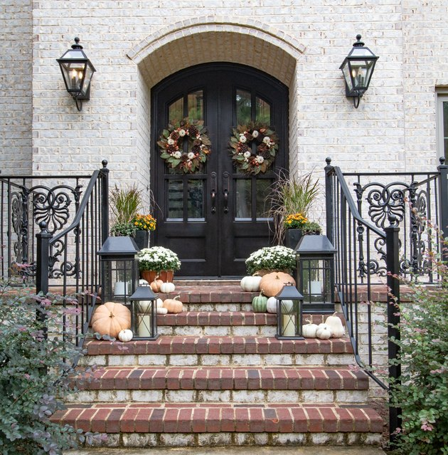 fall porch decor with white exterior with black door and pumpkins on steps