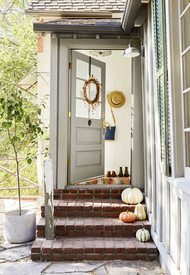 fall porch decor with wreath on door and pumpkins on steps