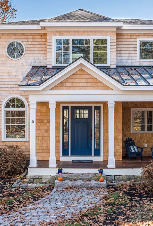 blue home exterior with unstained shingled roof and white accents