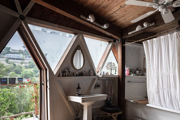 pedestal sink, shower/tub combo in front of triangular windows with view of the outside