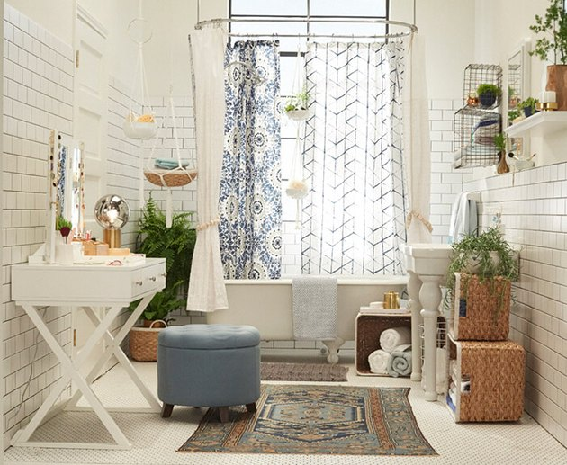 bohemian bathroom idea with subway tile walls and potted plants surrounding clawfoot tub