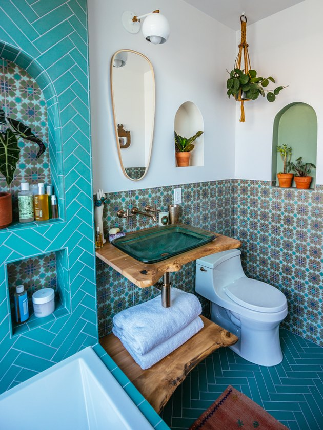 blue-green bohemian bathroom idea with glass vessel sink and live edge wood vanity and patterned wall tile with herringbone floor tile