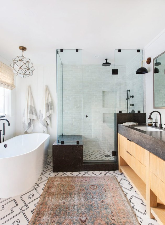 bohemian bathroom idea with glass shower enclosure and patterned floor tile