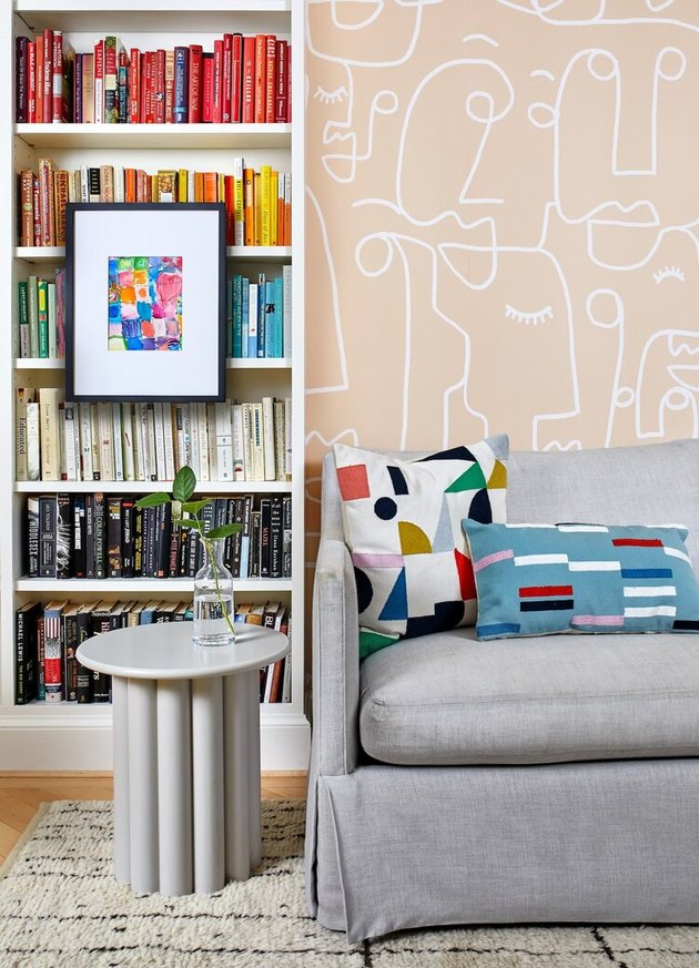 Wallpaper and color-coded books in a home office library by Zoe Feldman