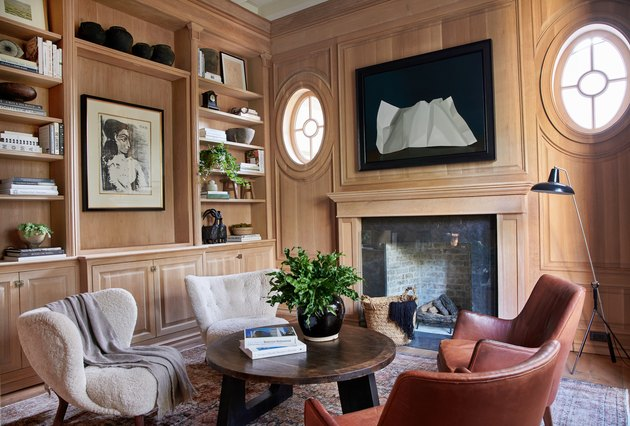 Home office library with wood walls and leather armchairs by Amber Interiors