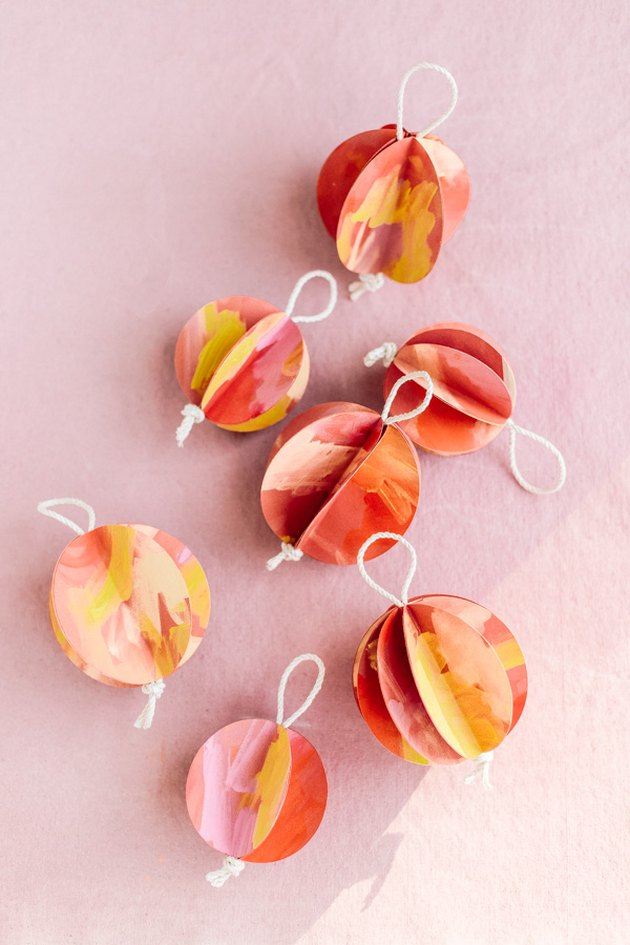 DIY Christmas decorations with colorful ornaments on pink background