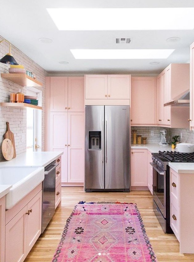pink kitchen color idea with wood flooring and white subway tile backsplash