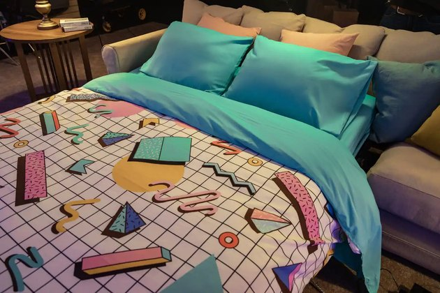 bed with bright bedding folding out from couch