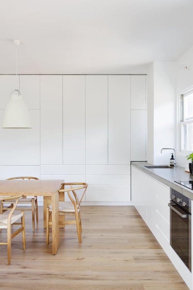 White floor-to-ceiling cabinets in minimalist kitchen with wood dining table and chairs