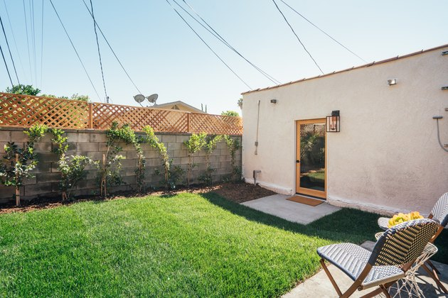 Spanish-style home with a green, freshly mowed yard; a concrete block fence and a blue patio chair are seen in the pho