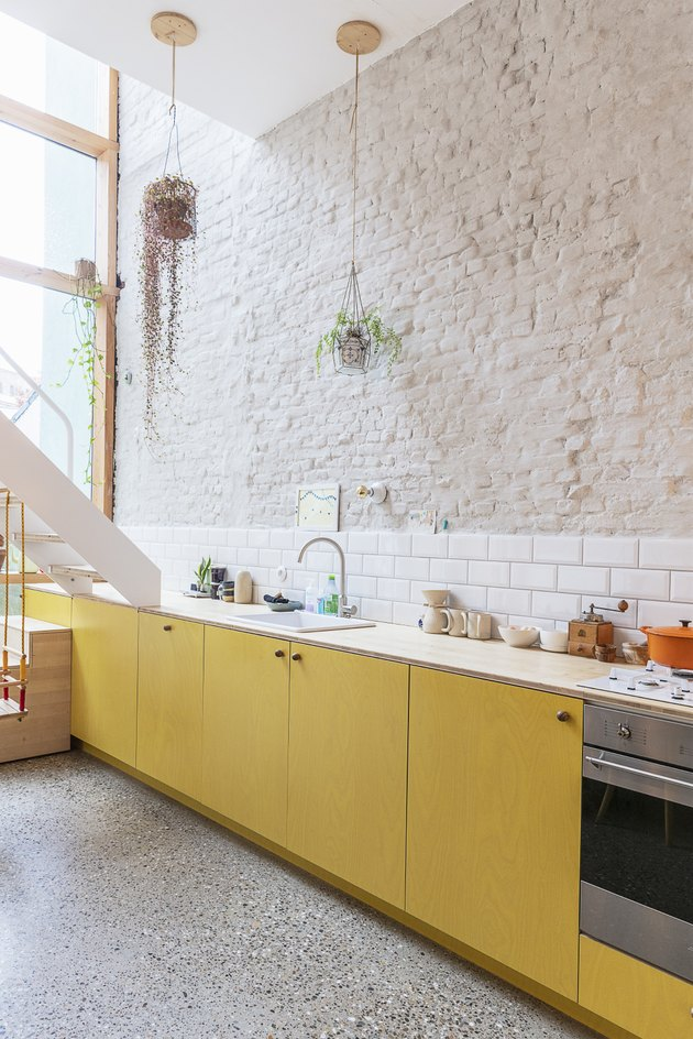 mellow yellow kitchen color trend with white brick wall and subway tile backsplash