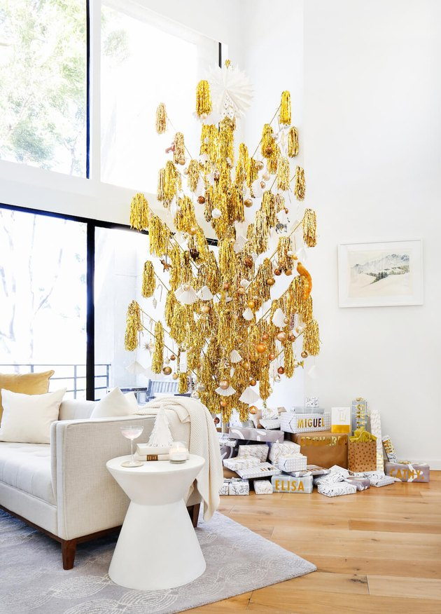 Christmas Tree Themes with Gold pompom Christmas tree, white couch, white side table, wood flooring.