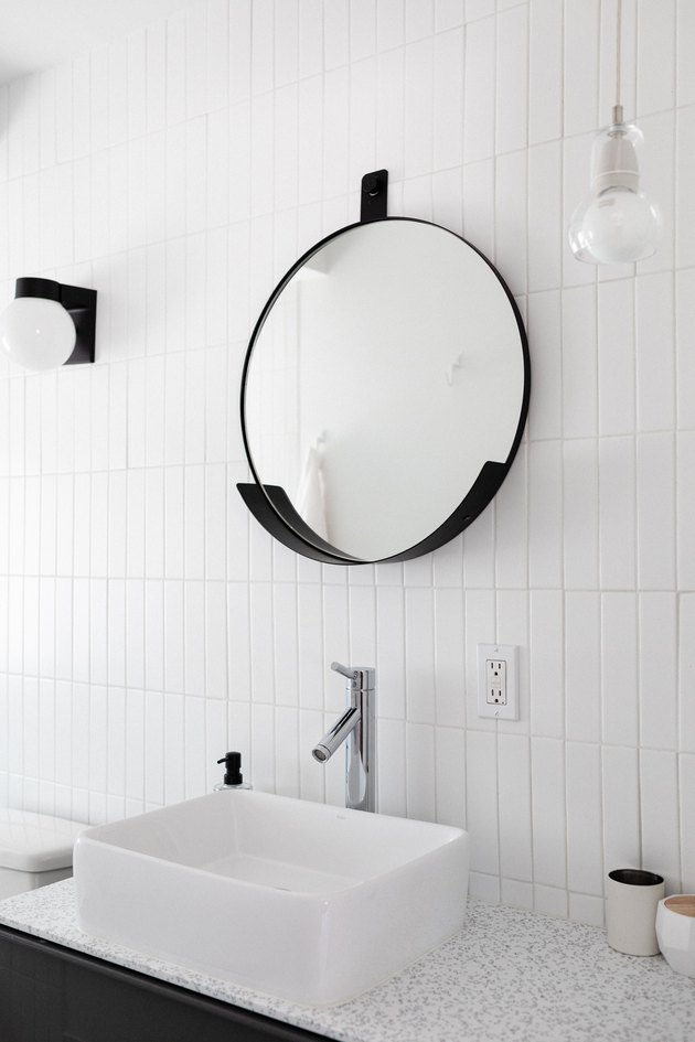 vessel bathroom sink with white wall tile and modern mirror