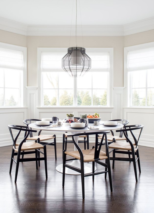 black and white dining room decor idea with wishbone chairs and bay windows
