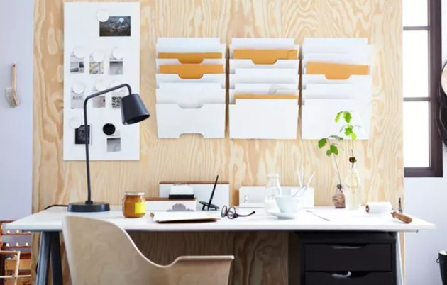 Home Office Organization Ideas with Plywood wall with hanging file holders, desk with black lamp, modern desk chair.