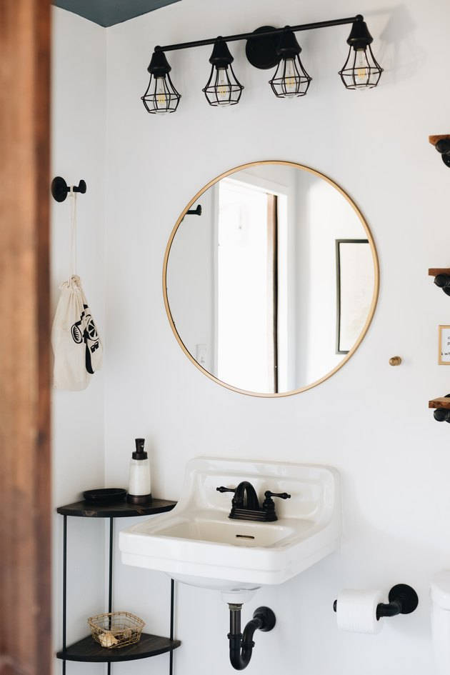 black and white bathroom with wall mount sink and matte black deck-mounted faucet