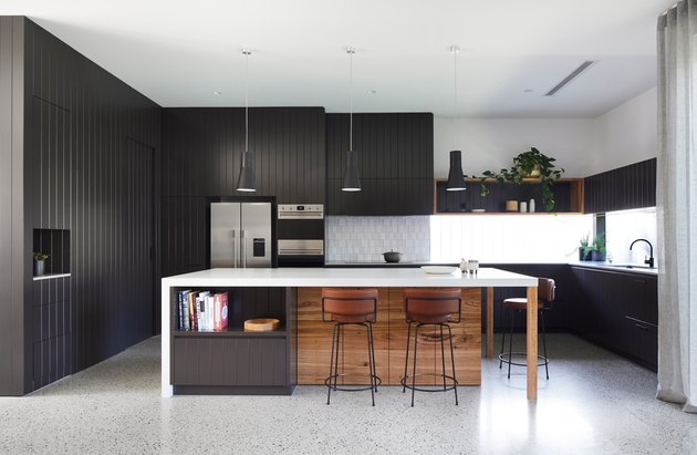 black and white kitchen with black panelling and large island