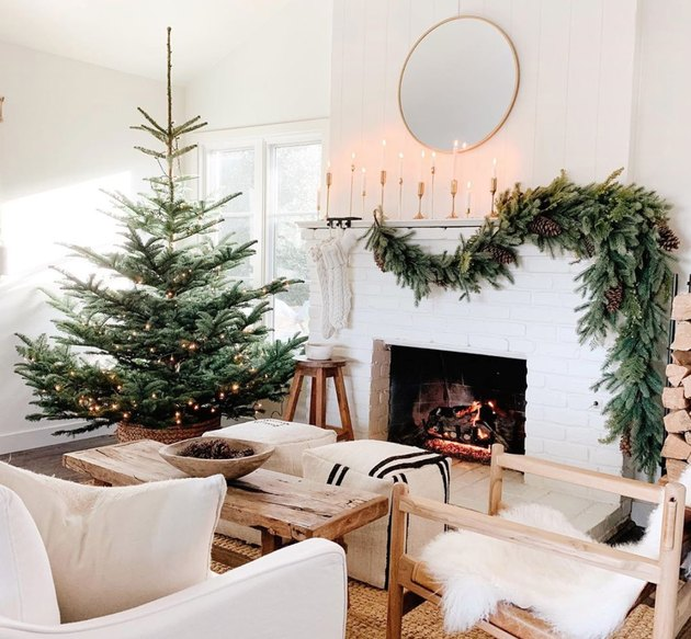 Christmas Tree Themes with Douglas fir Christmas tree, green garland on mantle, white brick fireplace, round mirror, candlesticks, white couch, sheepskin on side chair, rustic coffee table.