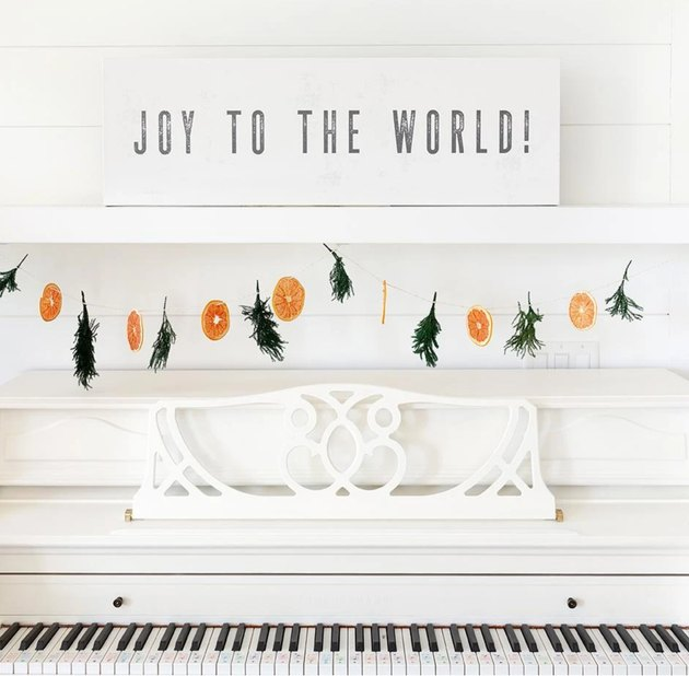 Joy to the World farmhouse Christmas decor with canvas sign on white piano with dried orange and juniper garland