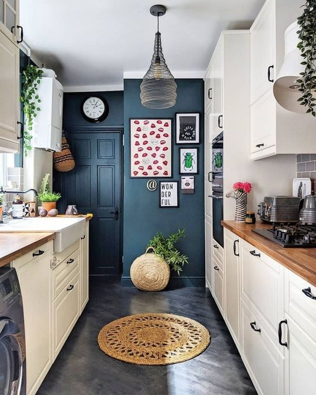 eclectic blue kitchen accent wall with white cabinets and farmhouse sink surrounded by plants