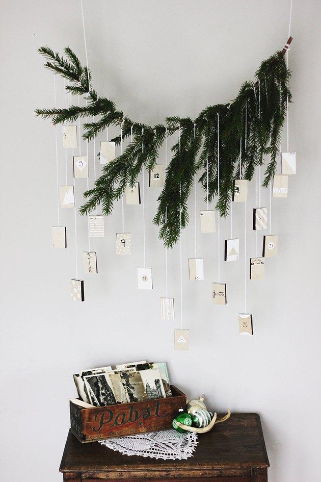 An advent calendar hanging from an evergreen limb