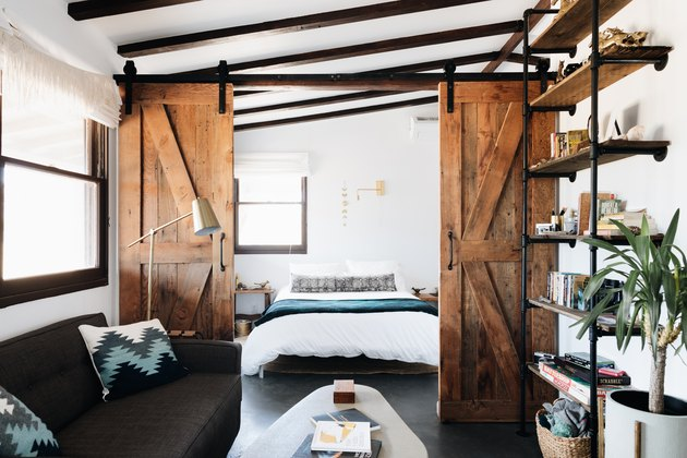 rustic modern cabin bedroom with barn doors and exposed ceiling beams