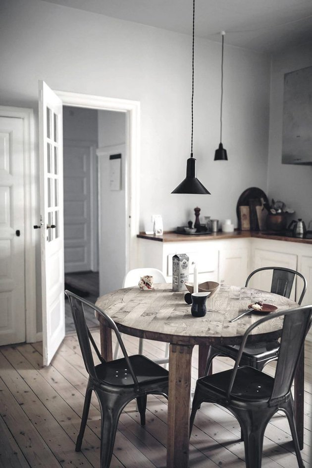 gray and white kitchen with rustic dining table and black pendant lights
