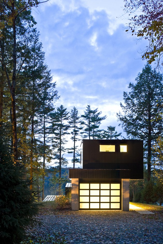 Bauhaus house with second story off-center and lights on in a pine forest