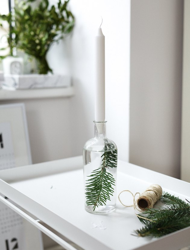 A candleholder with an evergreen twig in water