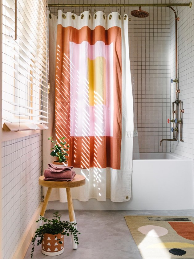 white bathroom with terra cotta color block shower curtain