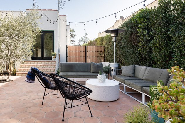 a patio outside of a Spanish-style home featuring Terracotta hexagon patio tiles, a gray outdoor couch, two black chairs, white round coffee table, a heat lamp and string lights