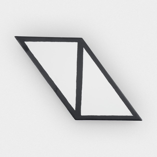 Piece of tile with two white triangles joined by black borders