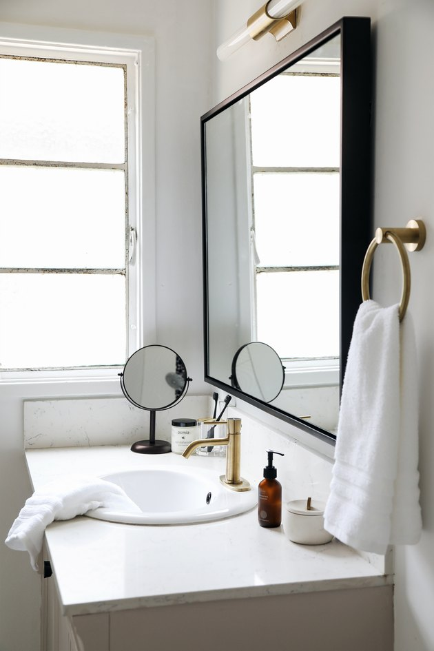 self-rimming bathroom sink with brass hardware and oversize mirror