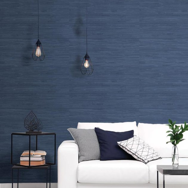 living room space with blue wallpaper and white couch